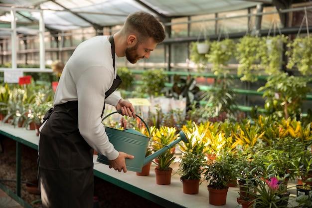 식물에 물을 주는 중형 남자