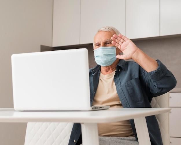 ノートパソコンで手を振っているミディアムショットの男