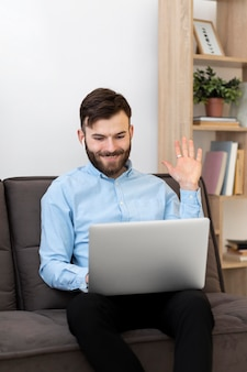 Средний выстрел мужчина машет ноутбуку