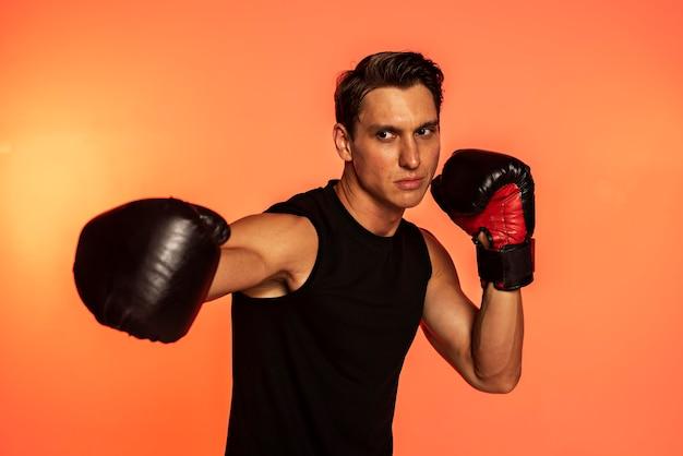 Medium shot man wearing boxing gloves