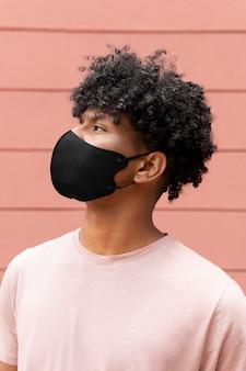 屋外でマスクを着用しているミディアムショットの男