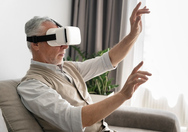 Medium shot man wearing vr glasses at home