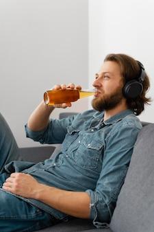 自宅で飲み物を持っているミディアムショットの男
