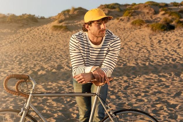 해변에서 자전거와 함께 중간 샷된 남자