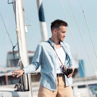 Medium shot man with camera on boat