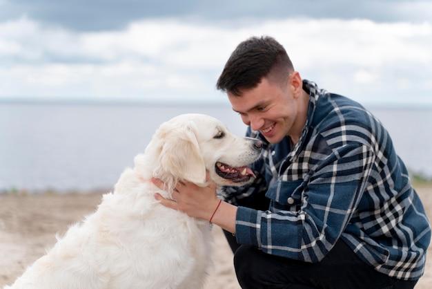 Средний выстрел человек с милой собакой на открытом воздухе
