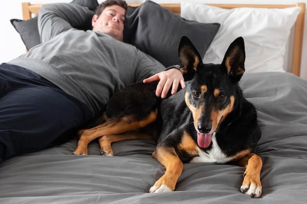 Средний выстрел мужчина с собакой в постели