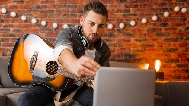 기타와 노트북 중간 샷된 남자