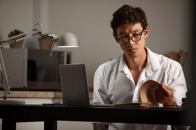 ノートパソコンと本を持ったミディアムショットの男