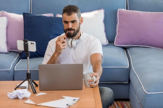 Uomo del colpo medio con il computer portatile a casa