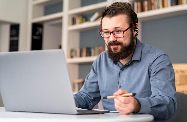 ノートパソコンを持ったミディアムショットの男