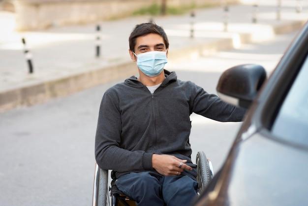 車の近くにマスクを持つミディアムショットの男