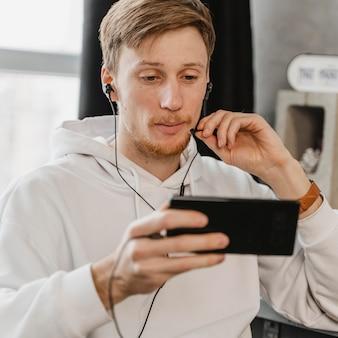 Uomo di tiro medio con telefono e auricolari