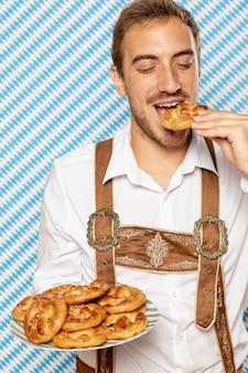 Medium shot of man with plate of pretzel