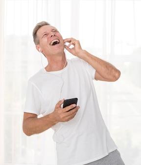笑ってスマートフォンでミディアムショット男