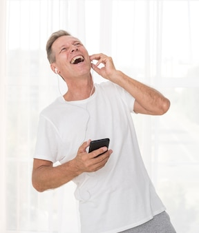 Medium shot man with smartphone laughing