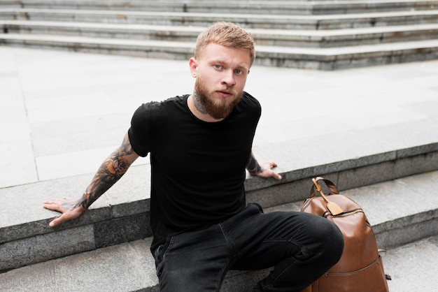Medium shot man with tattoos on arms