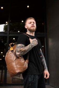 Medium shot man with tattoos and backpack