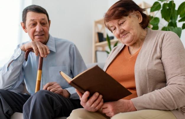 Colpo medio uomo e donna con il libro