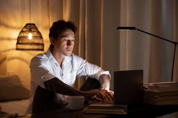 夜に自宅で働くミディアムショットの男