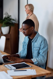 Uomo del colpo medio che lavora al computer portatile