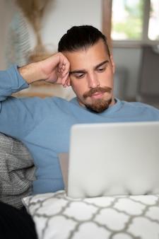 Medium shot man working on laptop