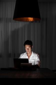Uomo a tiro medio che lavora di notte con il laptop