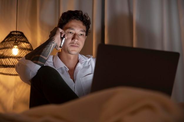 Средний выстрел человек, работающий на ноутбуке дома