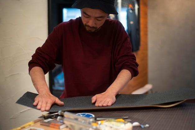 グリップテープで作業するミディアムショットの男