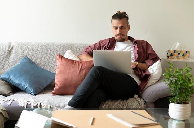 Средний выстрел человек, работающий с ноутбуком на диване