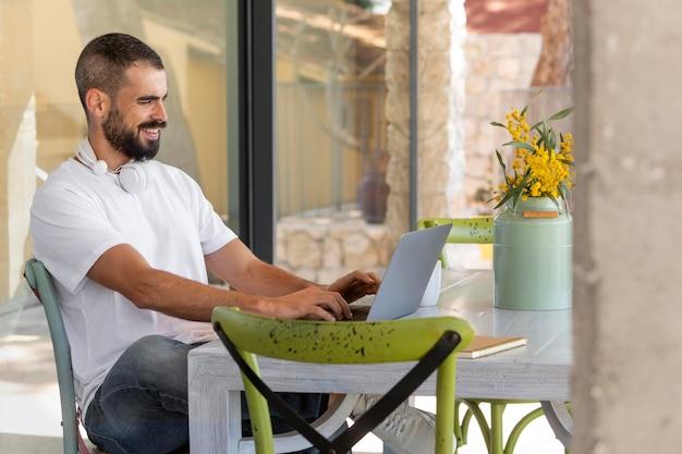 ノートパソコンで作業するミディアムショットの男
