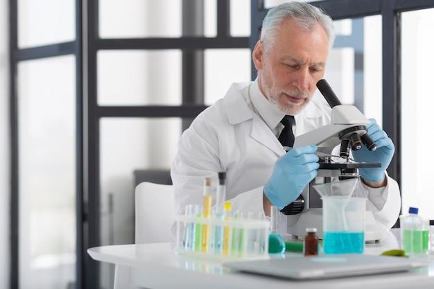 현미경으로 작업하는 중간 샷 남자