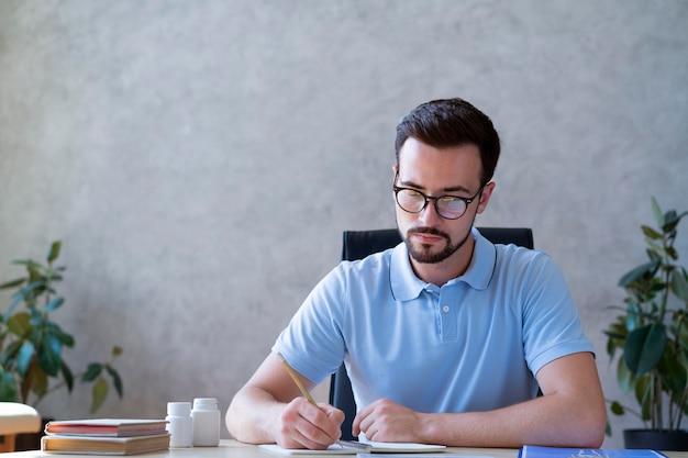 Medium shot man writing on paper