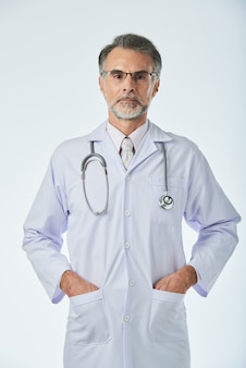 Medium shot of medical specialist standing with arms in pockets looking at camera