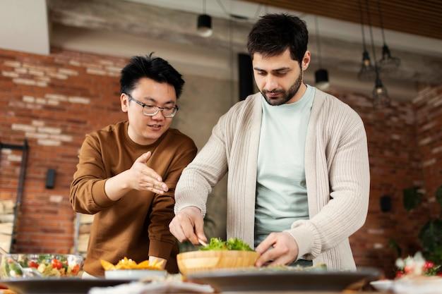 一緒に料理するミディアムショットの男性