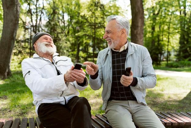 Medium shot men laughing on bench