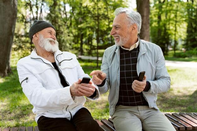 Uomini di tiro medio che ridono nel parco