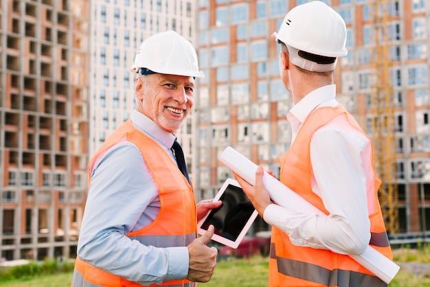 Medium shot men in safety vests with tablet