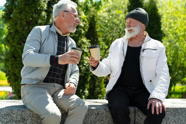 コーヒーカップを持つミディアムショットの男性