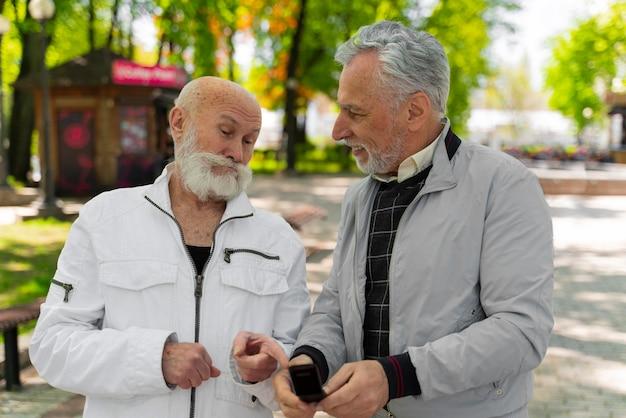 Uomini di tiro medio con il telefono all'aperto