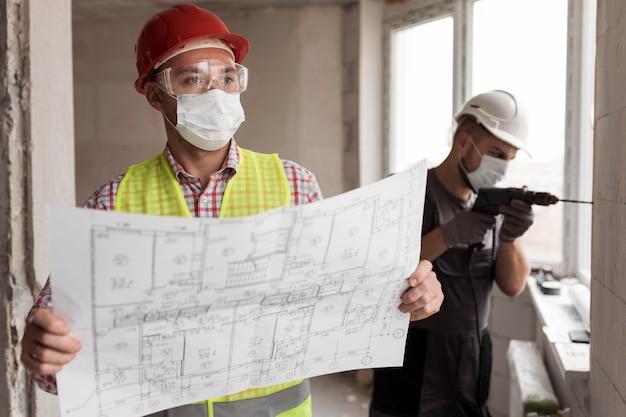 プロジェクトとドリルでミディアムショットの男性