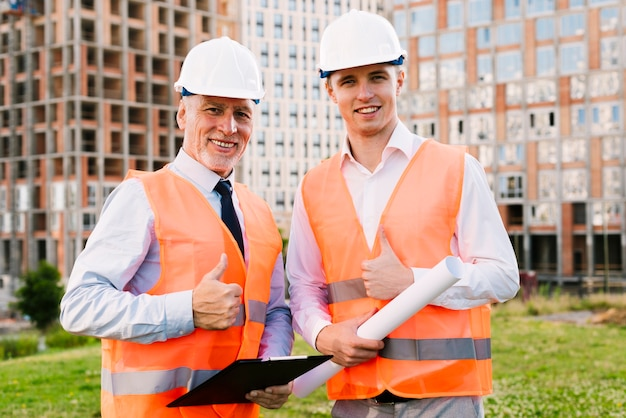Medium shot men with safety vests showing approval