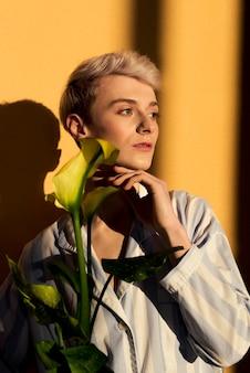 꽃과 함께 포즈를 취하는 중간 샷 모델