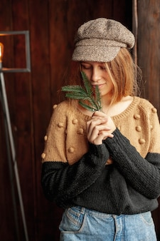 Medium shot model with fir tree twig and hat