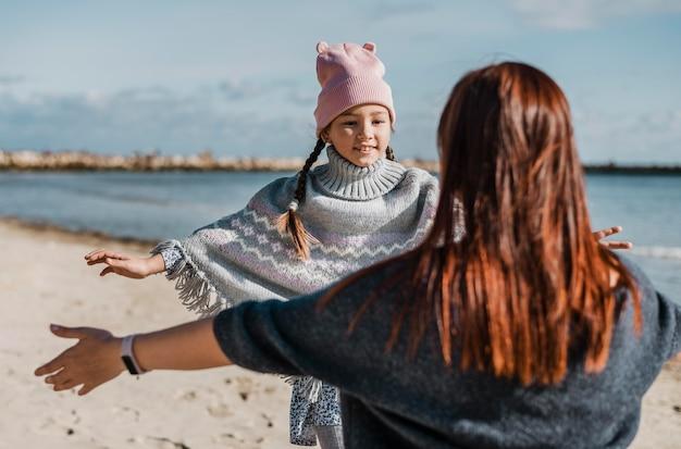 ビーチでミディアムショットの母と娘