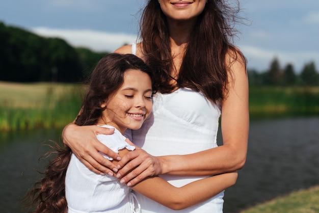 Средний выстрел, мать и дочь обнимаются у озера Бесплатные Фотографии