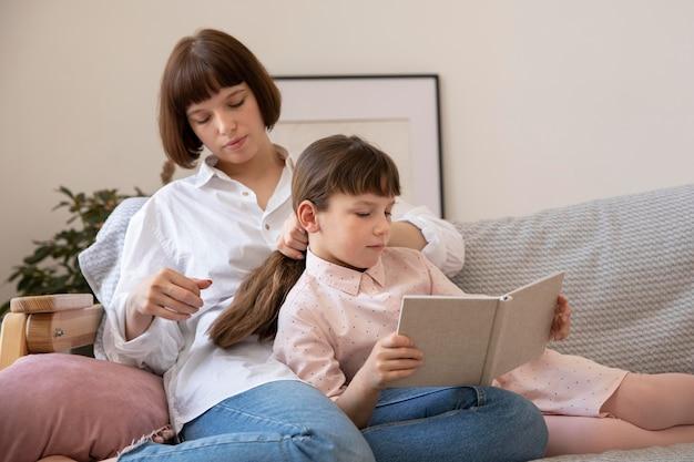 ミディアムショットの母と娘の読書本