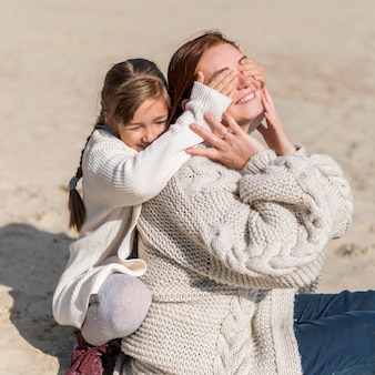 Мать и девочка среднего плана на пляже