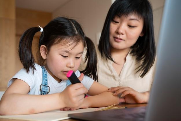 중간 샷 구슬 눈꼬리 및 여자 아이 책상 무료 사진