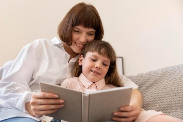 Мать и девочка, читающая книгу среднего размера Бесплатные Фотографии